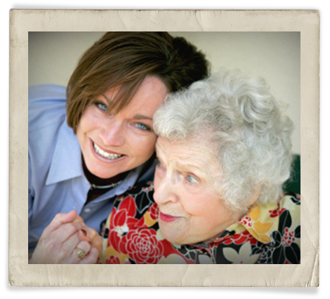 A young, blue-eyed caregiver hugs an older, white-haired woman.